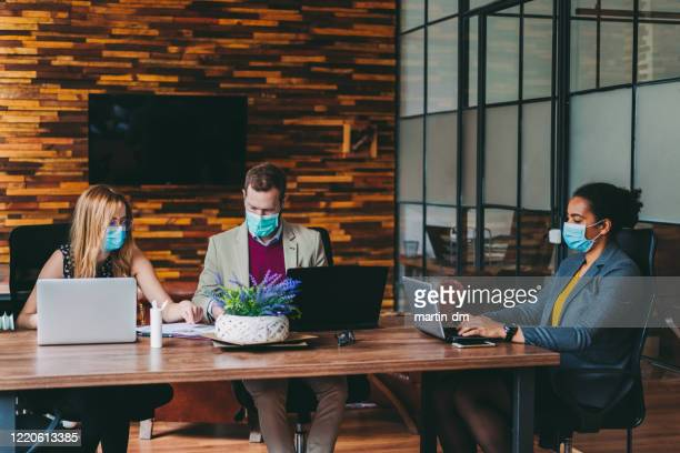 businesspeople working with face masks in the office during covid-19 pandemic - prevention stock pictures, royalty-free photos & images