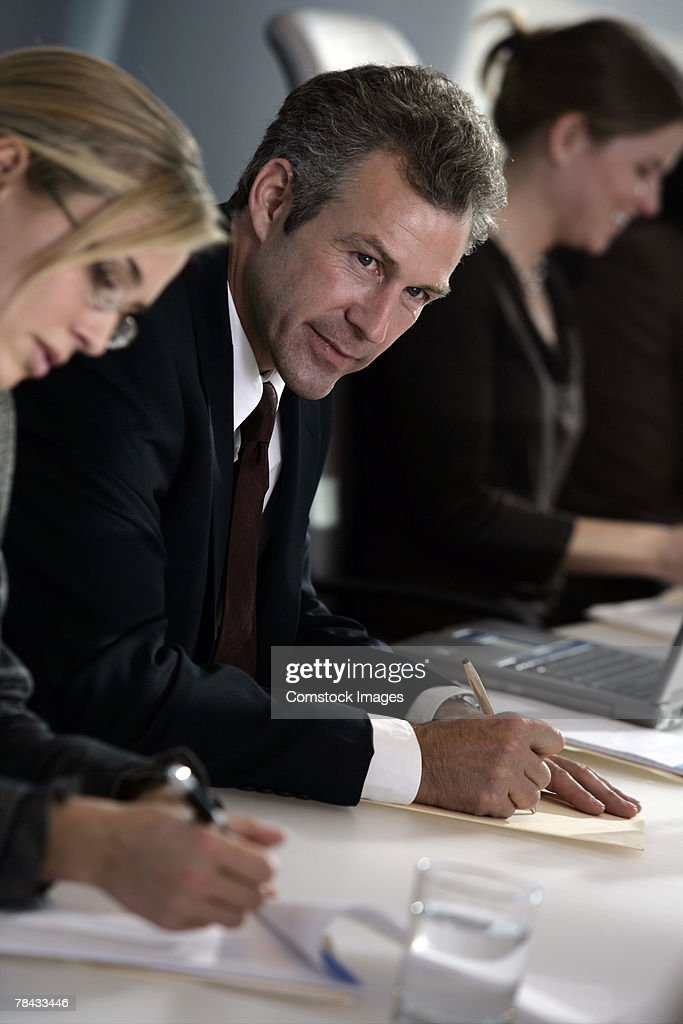 Businesspeople writing in meeting : Stockfoto