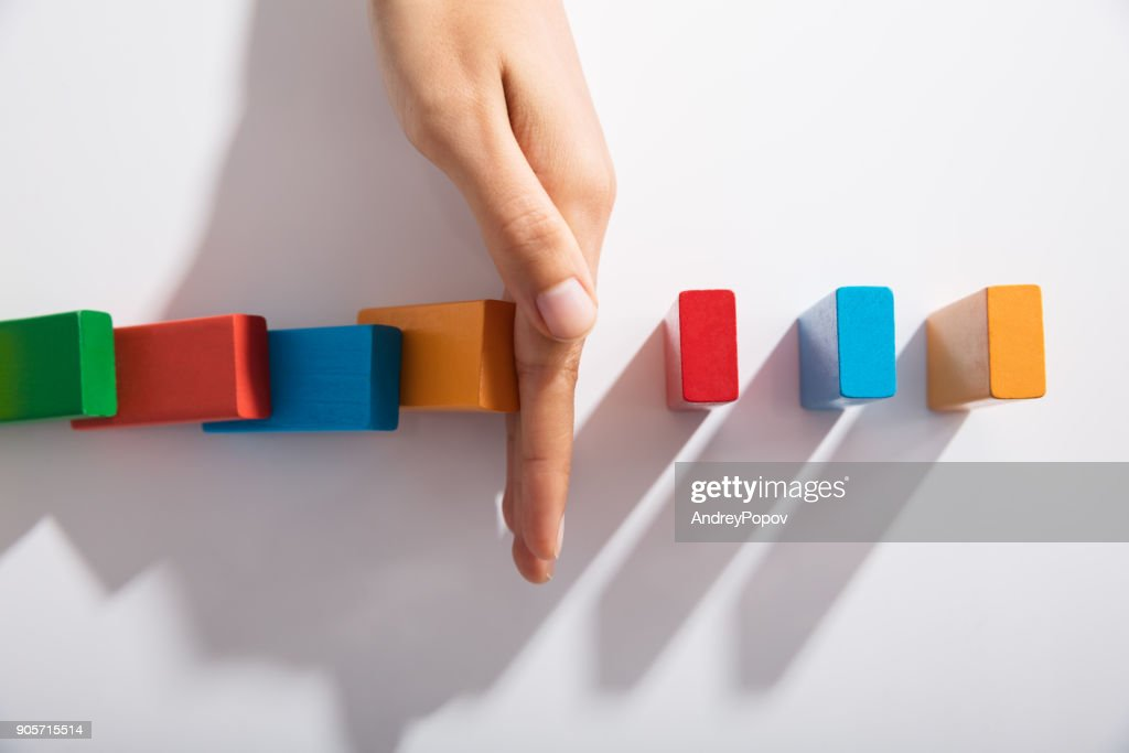 Businessperson Hand Stopping Colorful Blocks From Falling : Stock Photo