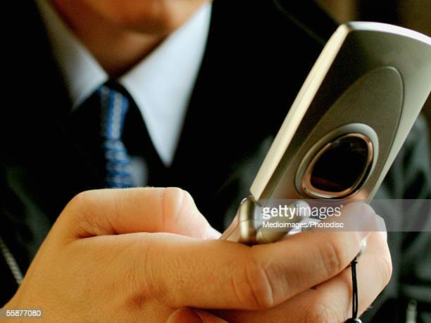 Businessperson holding and dialing cell phone