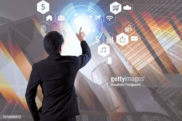 businessperson pushing icon on media screen and futuristic interface. internet of things. smart city. - financial technology bildbanksfoton och bilder