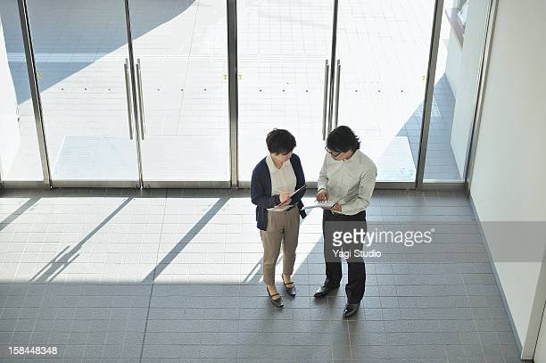 Businessperson talking in entrance hall of office