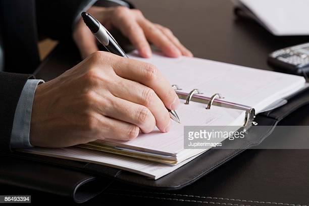 Businessperson writing in date book