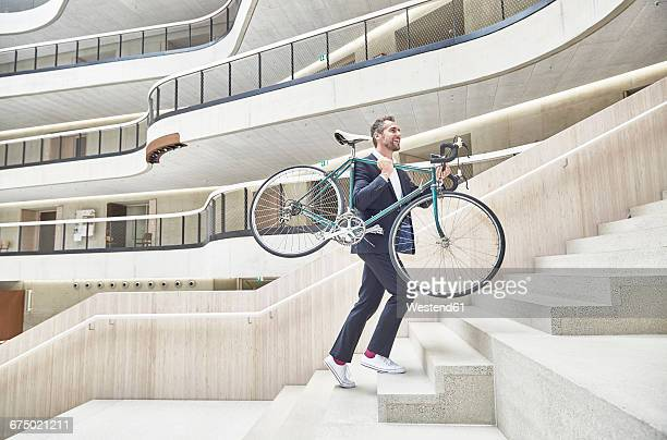 businesssman carrying bicycle in modern office building - fahrrad stock-fotos und bilder