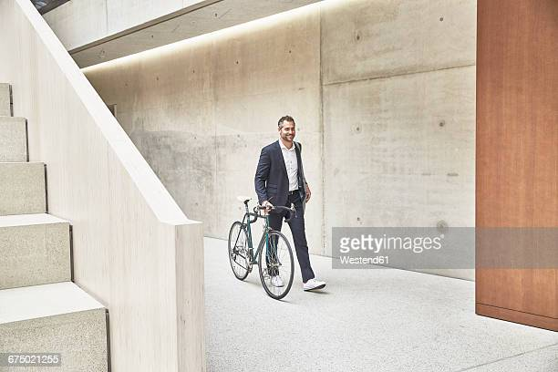 businesssman pushing bicycle along concrete wall - fahrrad stock-fotos und bilder