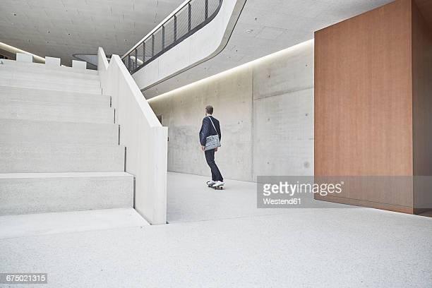 Businesssman riding skateboard along concrete wall in office building