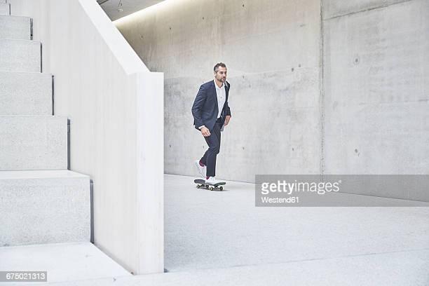 Businesssman riding skateboard along concrete wall