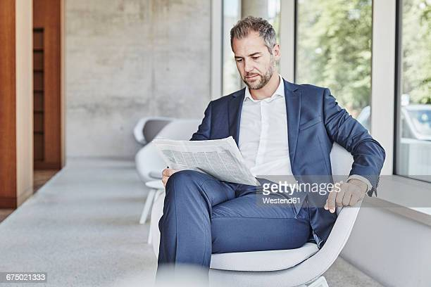 Businesssman sitting on chair reading newspaper