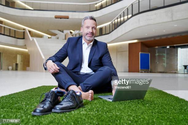 Businesssman sitting on synthetic turf using laptop