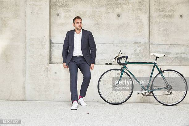 Businesssman with bicycle at concrete wall