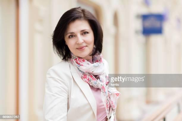 femme d'affaires de 50 ans dans une veste blanche - femme 50 ans brune photos et images de collection