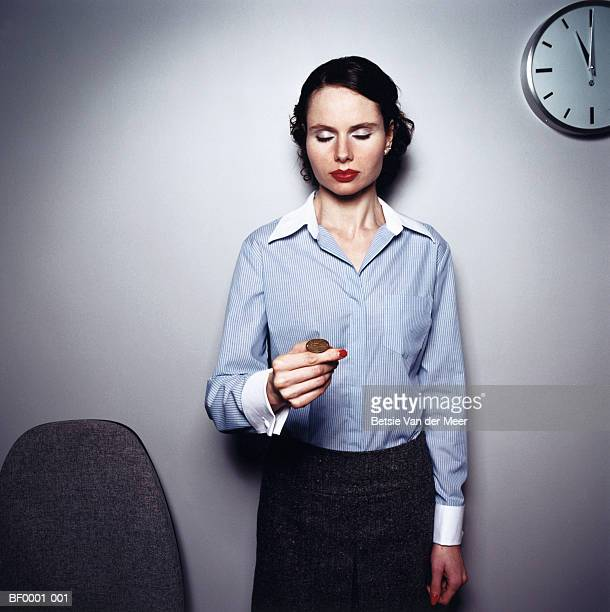 Businesswoman about to flip coin, eyes closed, portrait