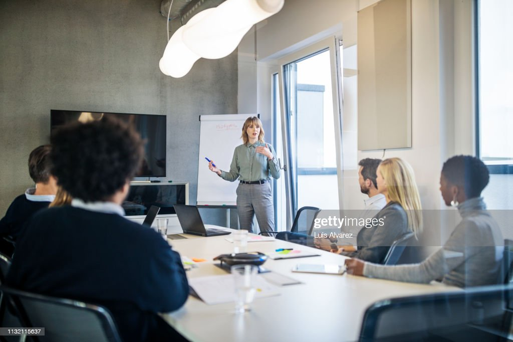 Businesswoman addressing a meeting around board table : Stock-Foto