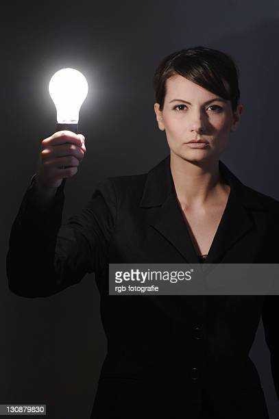Businesswoman, aged 24, with a light-bulb in her hand