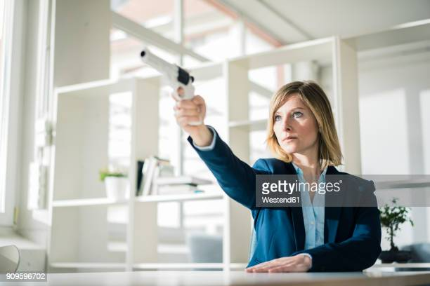 Businesswoman aiming with gun in office