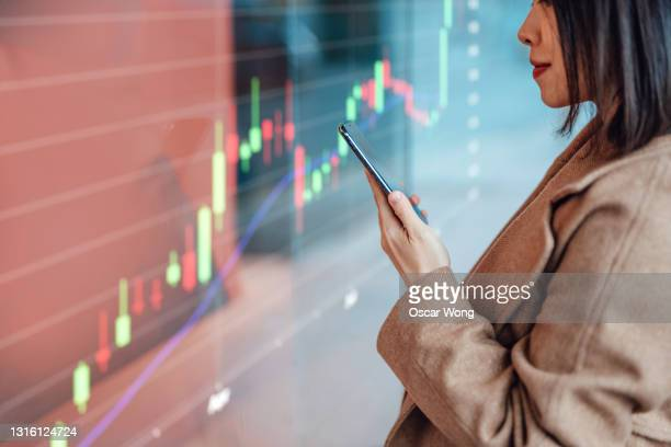 businesswoman analysing and checking stock market over smartphone in downtown financial district - bank stock pictures, royalty-free photos & images