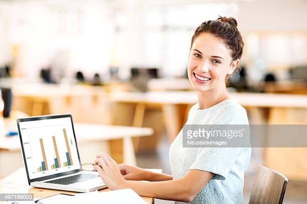 Businesswoman Analyzing Graph On Laptop At Desk