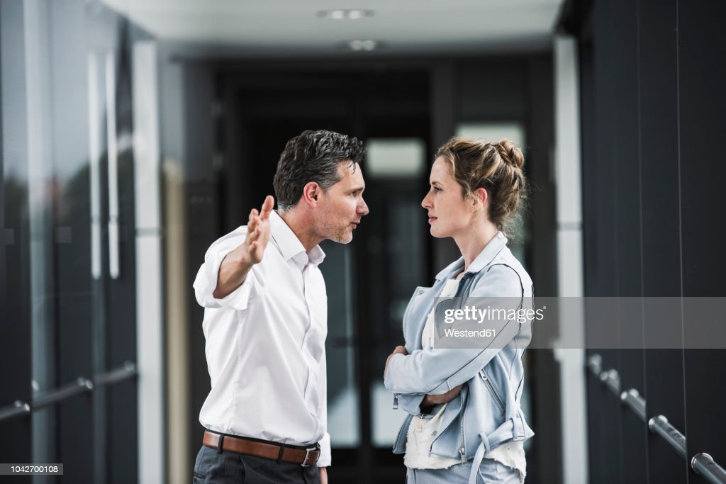Businesswoman and businessman arguing in office passageway : Stock Photo