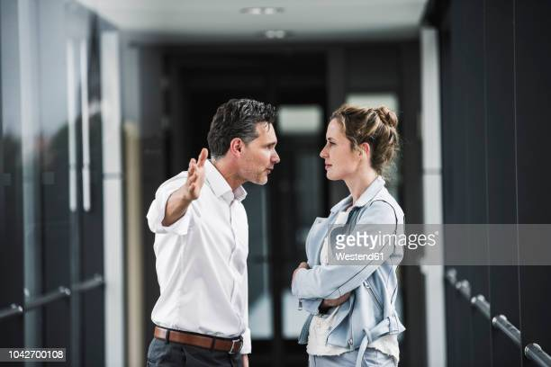 businesswoman and businessman arguing in office passageway - konflikt stock-fotos und bilder