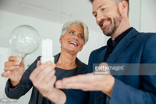 Businesswoman and businessman comparing regular and energy-saving lightbulb