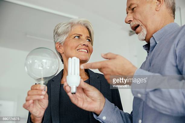 Businesswoman and businessman comparing regular and energy-saving lightbulb