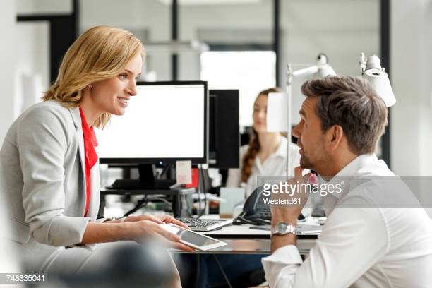 Businesswoman and businessman discussing at desk in office