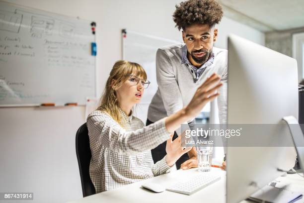 businesswoman and businessman discussing over computer in office - central europe stock photos and pictures