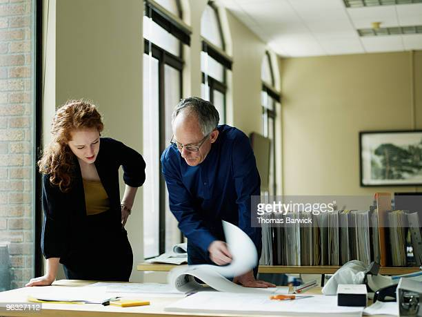 Businesswoman and businessman examining plans