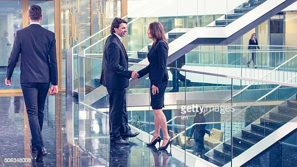 Businesswoman and businessman handshake in glass corridor