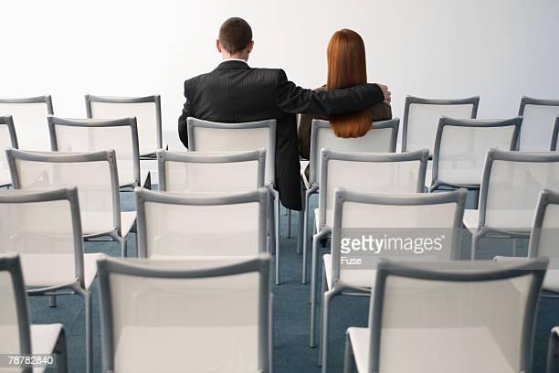 Businesswoman and Businessman in Auditorium