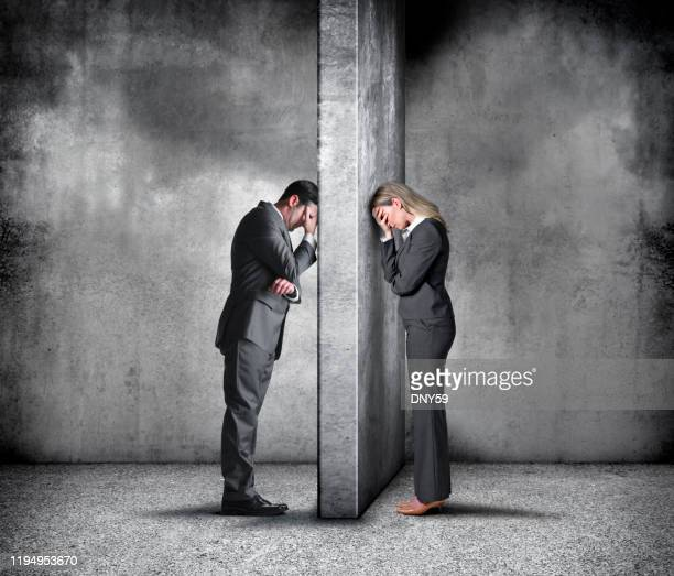 businesswoman and businessman leaning their heads against a wall - communication problems stock pictures, royalty-free photos & images