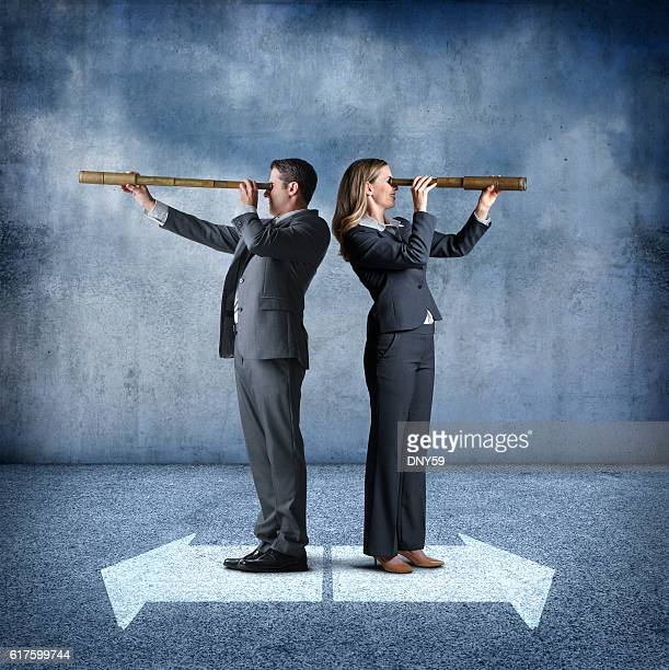 Businesswoman And Businessman Look Through Spyglasses Pointing In Opposite Directions