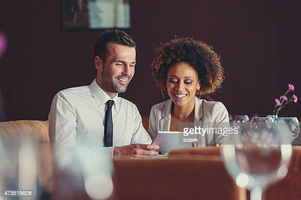 Businesswoman and businessman on lunch using digital tablet