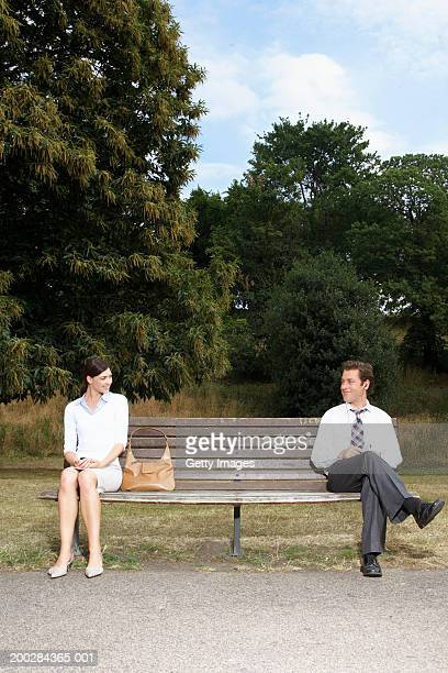Businesswoman and businessman on park bench, looking at each other