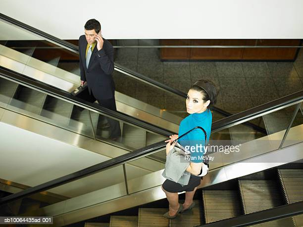 businesswoman and businessman passing on opposite escalators - moving past stock pictures, royalty-free photos & images