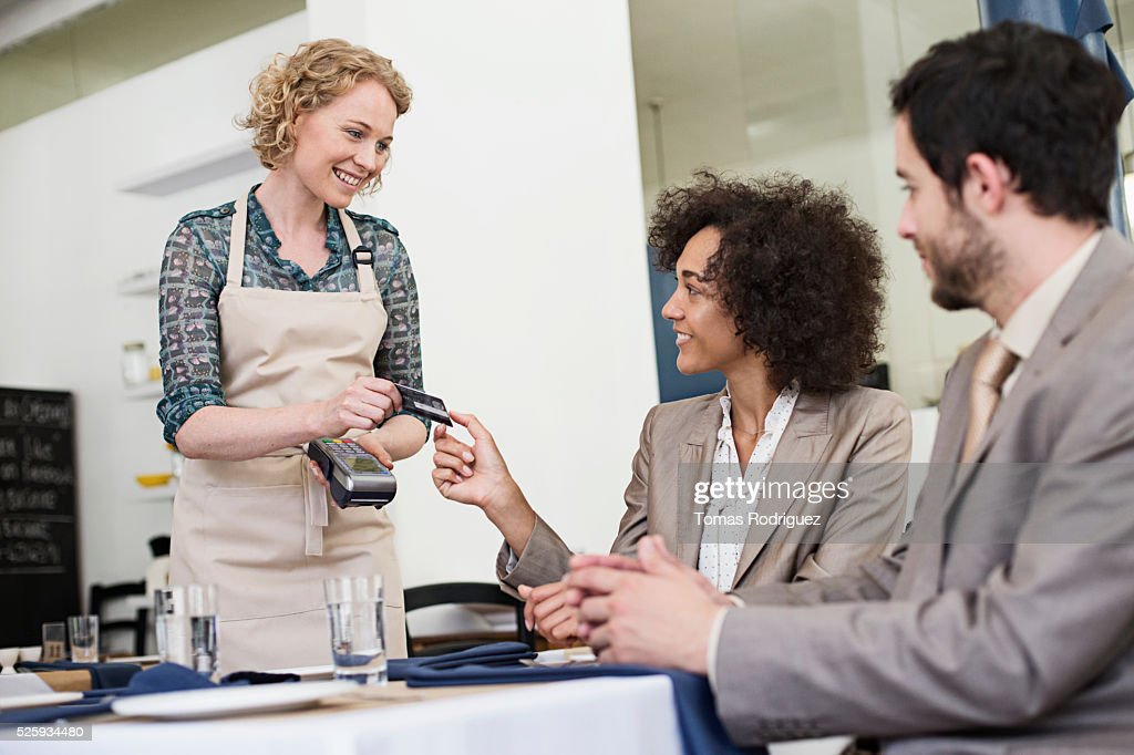 Businesswoman and businessman paying with credit card in restaurant : Stock Photo