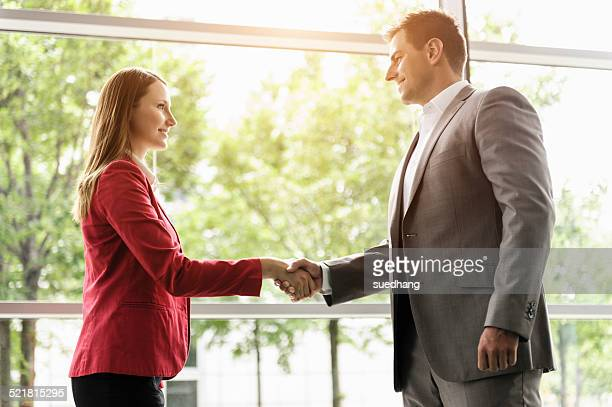 businesswoman and businessman shaking hands - red suit stock pictures, royalty-free photos & images