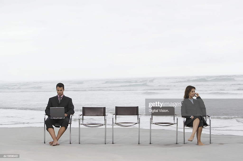 Businesswoman and Businessman Sitting Apart on a Beach Using a Laptop and a Mobile Phone : Stock Photo