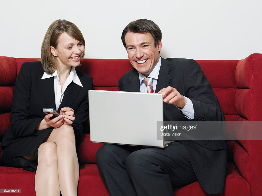 Businesswoman and Businessman Sitting on a Sofa With a Laptop : Stock Photo