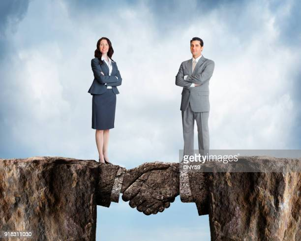businesswoman and businessman stand on cliffs joined by stone handshake - bridging the gap stock photos and pictures