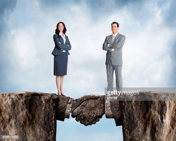 empresária e empresário fica nas falésias que se juntaram a pedra aperto de mão - estabelecer uma ponte - fotografias e filmes do acervo