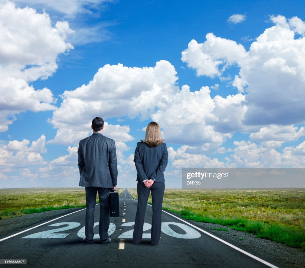 Businesswoman And Businessman Stand On Long Road With The Year 2020 Painted On It : Stock Photo