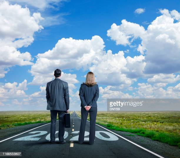 businesswoman and businessman stand on long road with the year 2020 painted on it - vision 2020 stock photos and pictures