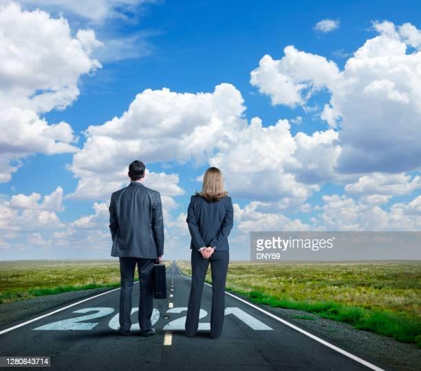 affärskvinna och affärsman står på long road med året 2021 målade på den - anticipation bildbanksfoton och bilder