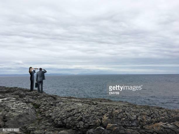Unternehmerin und Unternehmer stehen auf felsigen Klippen mit Blick auf ominösen Himmel und Rough Sea