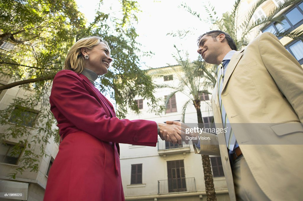 Businesswoman and Businessman Stand Outdoors, Shaking Hands : Stock Photo
