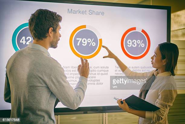 businesswoman and businessman talking about market share - pie chart stock pictures, royalty-free photos & images