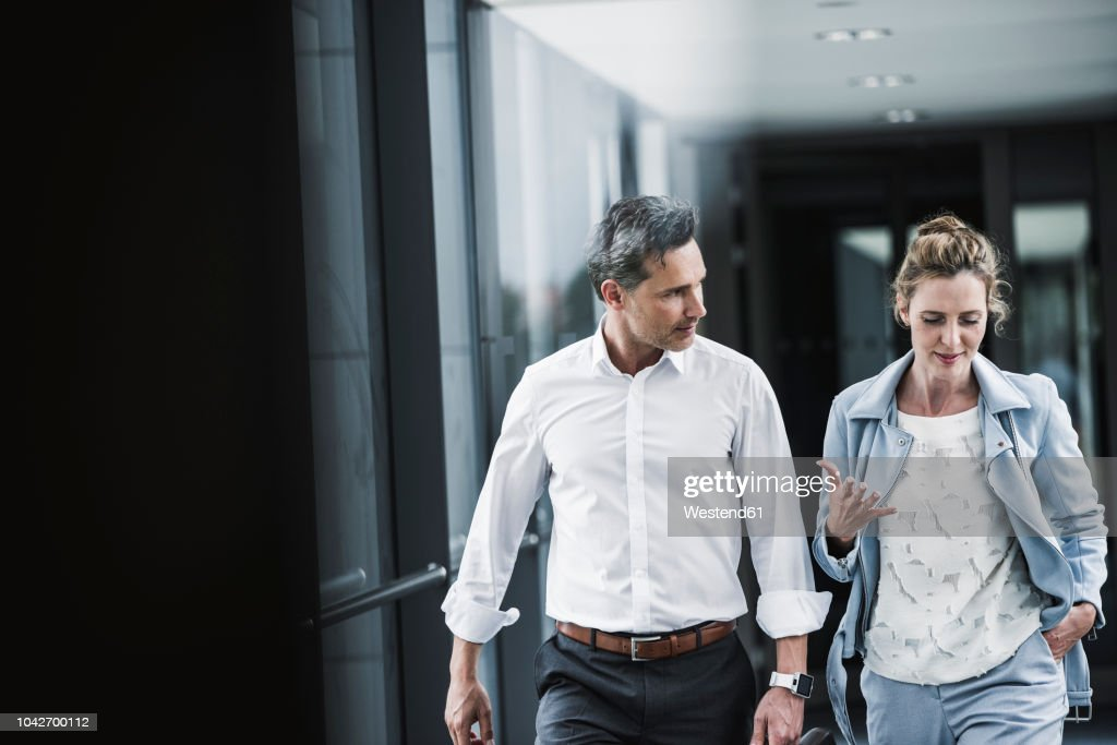 Businesswoman and businessman talking in office passageway : Stock-Foto