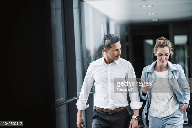businesswoman and businessman talking in office passageway - parlare foto e immagini stock
