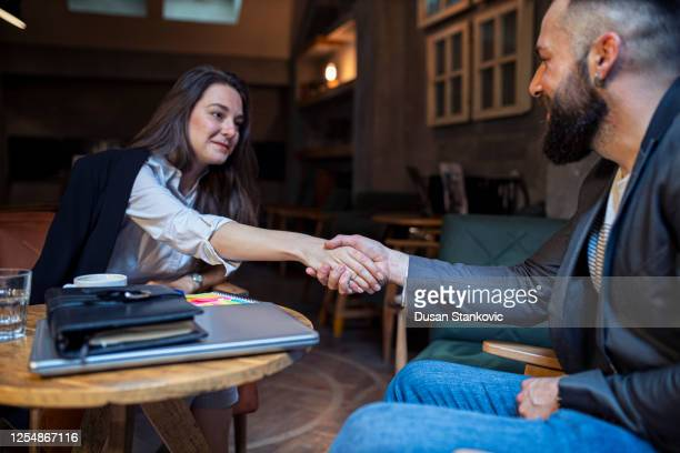 businesswoman and businessman talking in the coffee place - alternative lifestyle stock pictures, royalty-free photos & images